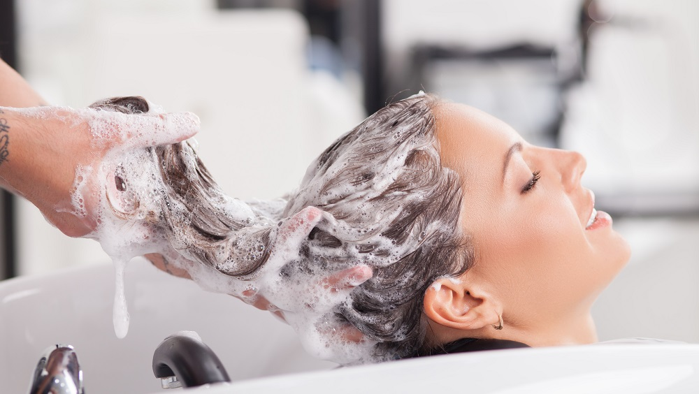 Close up of face of beautiful woman is getting a hairwash by a hairdresser. She is smiling. Her eyes are closed with relaxation. The beautician is making foam from shampoo